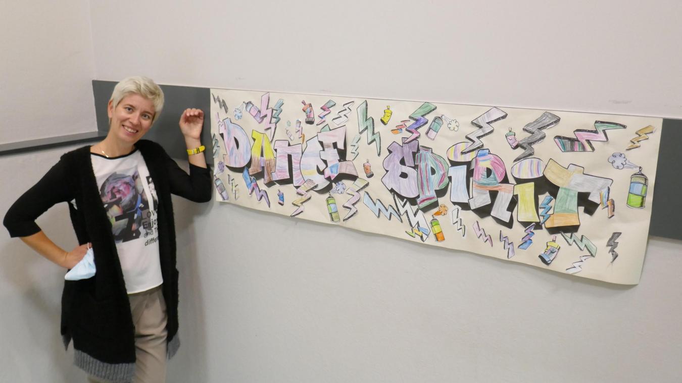 Aurélie devant un graffiti, résultat d'un travail collectif réalisé par les élèves de 4-6 ans en stage d'éveil artistique sur le thème des danses urbaines.