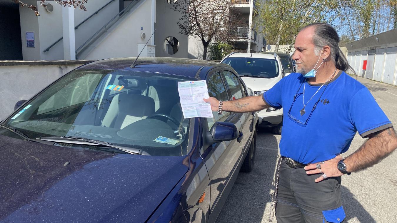 Sous le pare-brise, sa carte de stationnement, dans sa main, sa contravention.